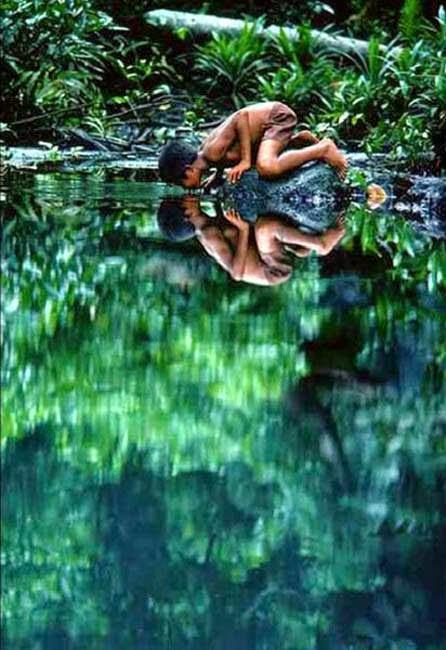 Nino bebiendo agua de la naturalesa